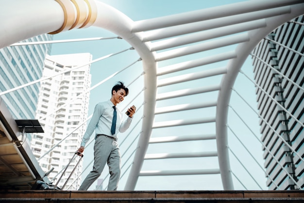 Homem de negócios novo feliz using mobile phone ao andar com a mala na cidade. estilo de vida das pessoas modernas. vista de ângulo baixo. comprimento total. cidade urbana moderna