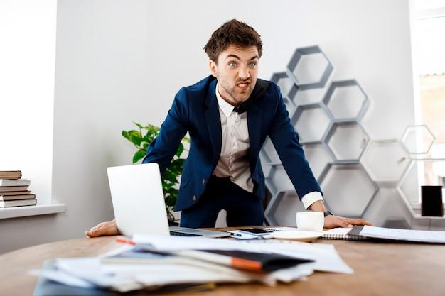 Homem de negócios novo irritado que está no local de trabalho, fundo do escritório.