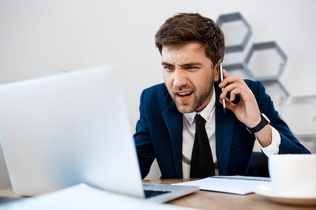 Homem de negócios novo irritado que fala no telefone, fundo do escritório.