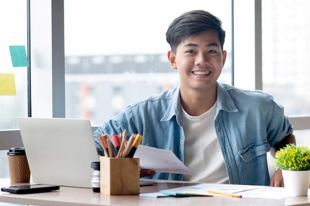 Homem de negócios novo na roupa ocasional que senta-se em sua mesa no escritório.