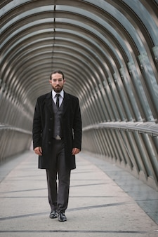 Homem de negócios novo que anda na ponte pedestre futurista no distrito da defesa. paris, frança.
