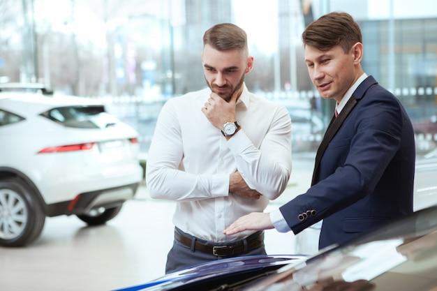 Homem de negócios novo que compra o automóvel novo