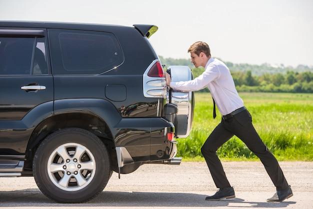Homem de negócios novo que empurra um carro com depósito de gasolina vazio.