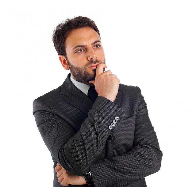Homem de negócios novo que pensa e que reflete.