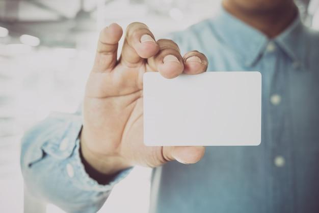 Homem de negócios novo que prende o cartão de visita branco no fundo moderno do borrão do escritório.