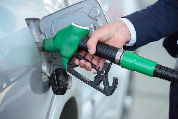 Homem de negócios novo que reabastece o tanque do carro na estação do combustível.