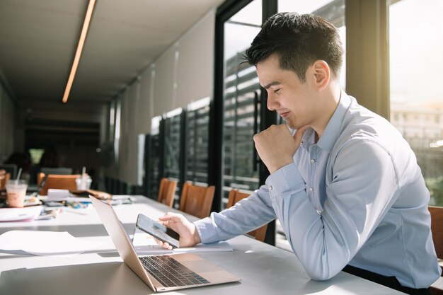 Homem de negócios novo que senta-se em sua mesa no escritório que olha o telefone esperto com sorriso.