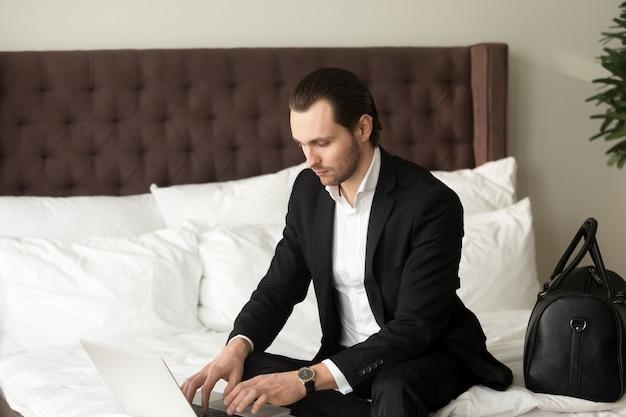 Homem de negócios novo que senta-se na cama que trabalha no portátil no hotel.