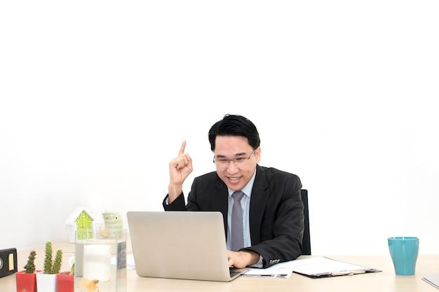 Homem de negócios novo que trabalha com fontes do portátil e de escritório.