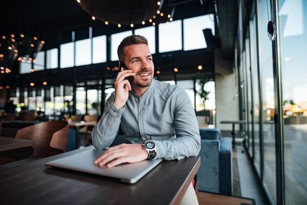 Homem de negócios ocasional considerável que fala no telefone celular no café moderno.