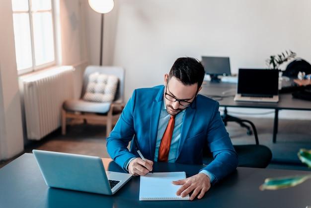 Homem de negócios ocupado escrevendo notas em papel.