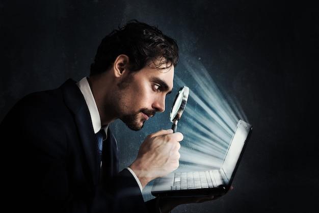 Homem de negócios olha com lupa para a tela do computador