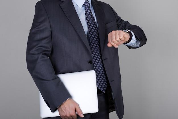 Homem de negócios olha para o relógio de pulso, verificando as horas. conceito de gerenciamento de tempo e prazo