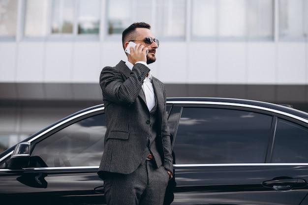Homem de negócios pelo carro falando ao telefone