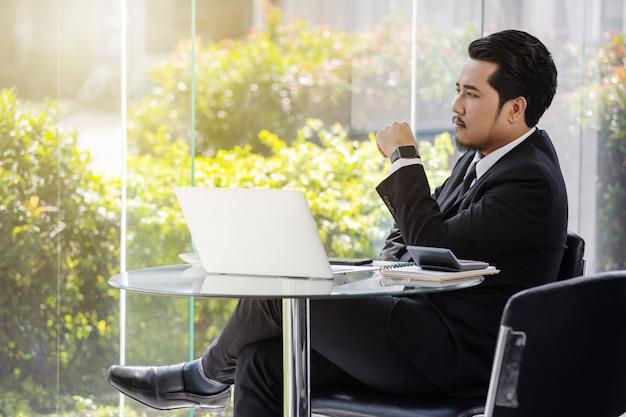Homem de negócios, pensando e trabalhando com o computador portátil