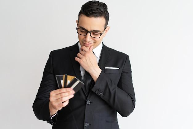 Homem de negócios pensativo da raça misturada que olha cartões de crédito.