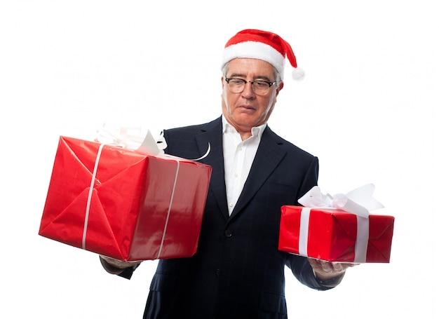 Homem de negócios pensativo que prende dois presentes de natal