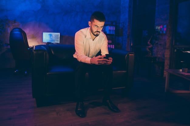 Homem de negócios pensativo segurando a tela do telefone