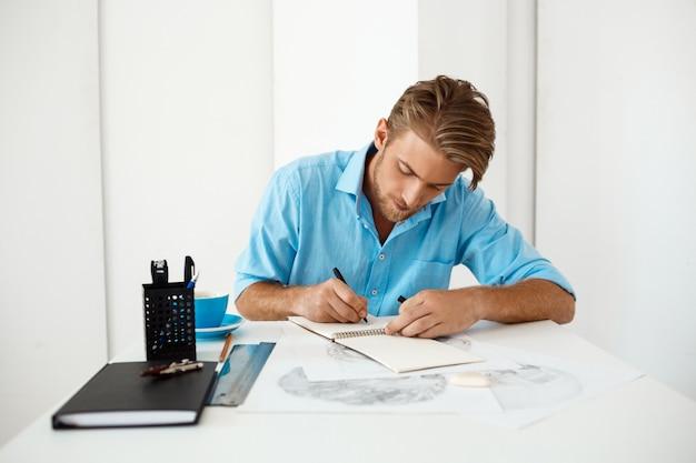 Homem de negócios pensativo seguro considerável novo que senta-se na tabela com o retrato do desenho de lápis. interior de escritório moderno branco.