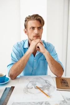 Homem de negócios pensativo seguro considerável novo que senta-se na tabela que pensa sobre o retrato do desenho de lápis. interior de escritório moderno branco.