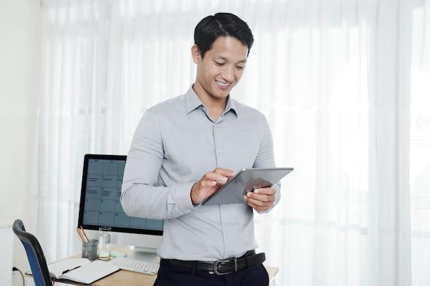 Homem de negócios positivo com tablet digital