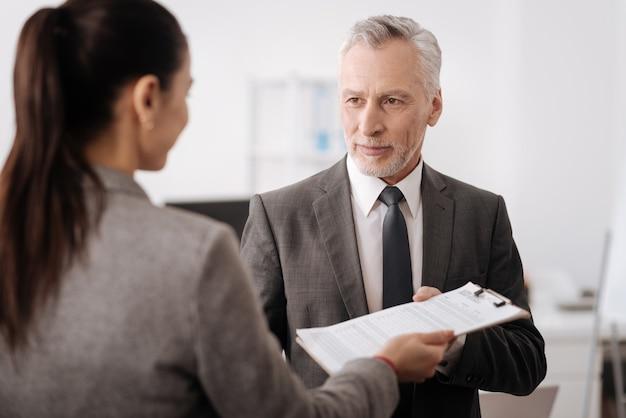 Homem de negócios positivo vestindo roupas inteligentes olhando para o lado enquanto se reúne com seu colega de trabalho