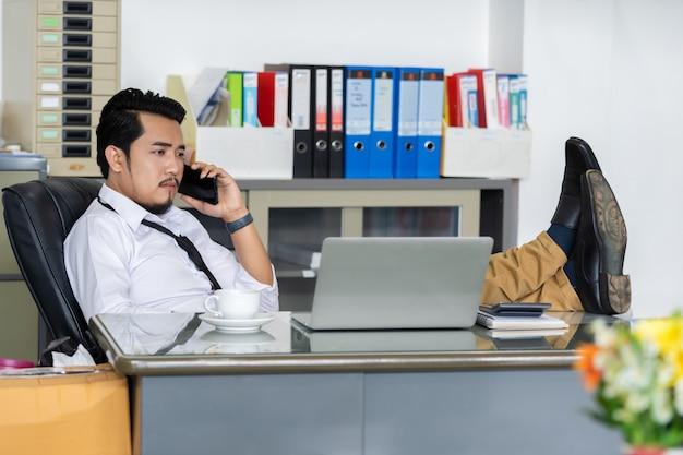 Homem de negócios preguiçoso falando no celular com os pés na mesa no escritório