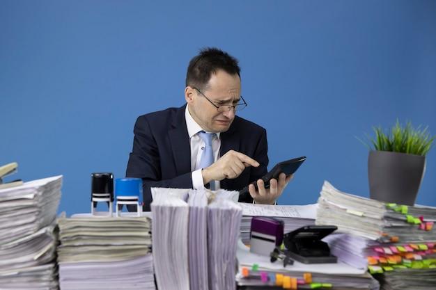 Homem de negócios preocupado e chorando considera as perdas na calculadora sentado à mesa com pilhas de papéis no escritório