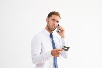 Homem de negócios preocupado segurando o cartão de crédito e falando