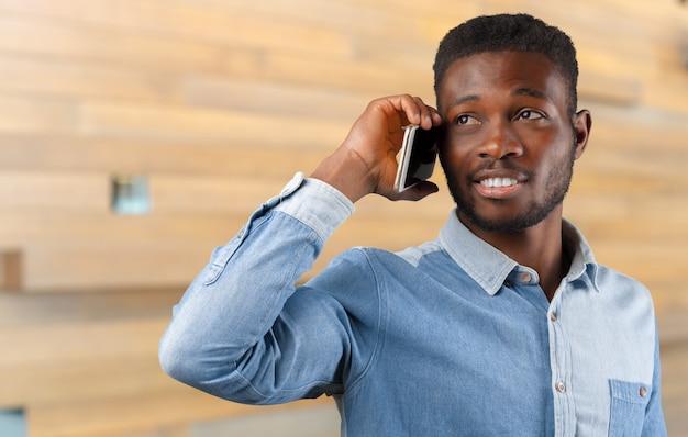 Homem de negócios preto jovem usando seu telefone celular