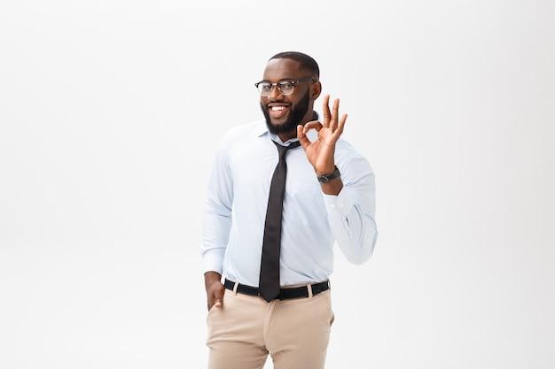 Homem de negócios preto novo que tem o olhar feliz, sorrindo, gesticulando, mostrando o sinal aprovado.