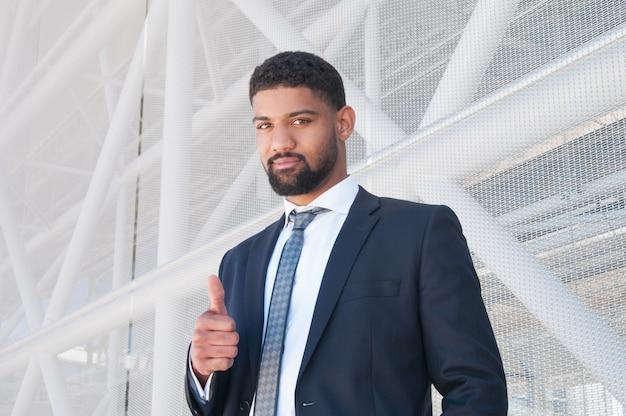 Homem de negócios preto sério aparecendo polegar