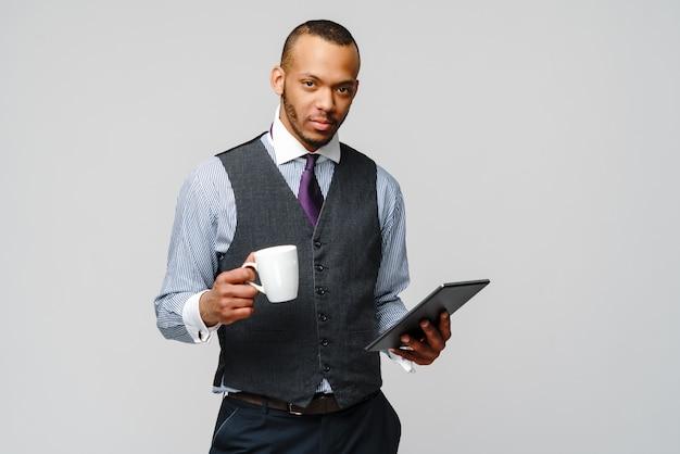 Homem de negócios profissional afro-americano segurando o tablet pc e café.