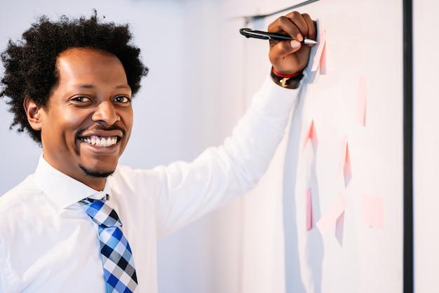 Homem de negócios profissional usando notas auto-adesivas no quadro branco para compartilhar ideias para o plano de estratégia de negócios. conceito de negócios.