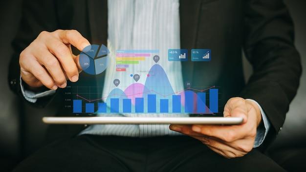 Homem de negócios que analisa a empresa financeira trabalhando com gráficos digitais da realidade aumentada.