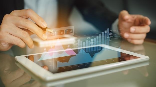 Homem de negócios que analisa dados financeiros do fundo mútuo da empresa com tecnologia digital dos gráficos da realidade aumentada.