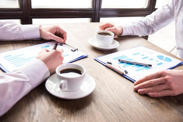 Homem de negócios que analisa gráficos com xícara de café.