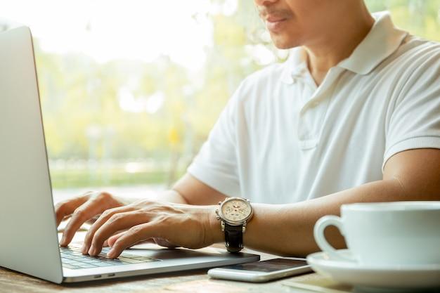 Homem de negócios que datilografa no portátil com a xícara de café na tabela no café.