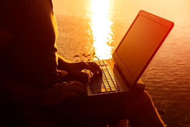 Homem de negócios que datilografa o portátil moderno contra a paisagem bonita do por do sol na noite.