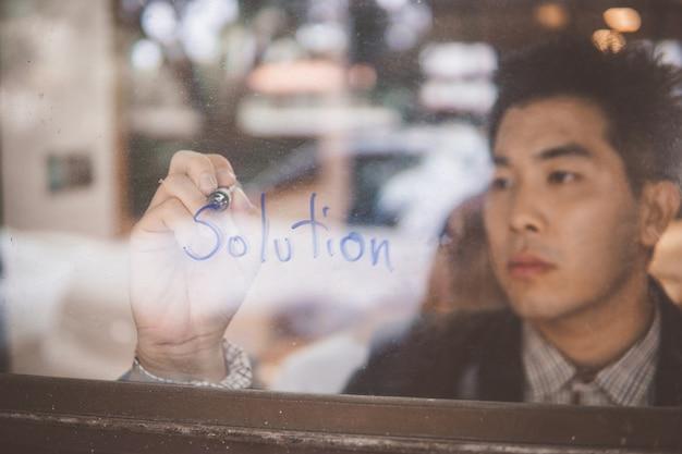 Homem de negócios que escreve um conceito das soluções do negócio na janela.