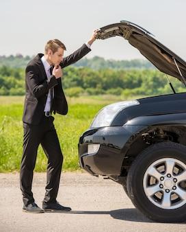 Homem de negócios que examina o motor de automóveis dividido no campo.
