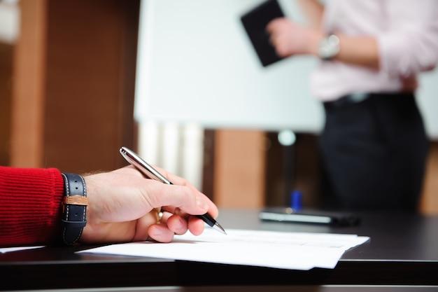 Homem de negócios que explica o plano de negócios aos colegas de trabalho na sala de conferências.