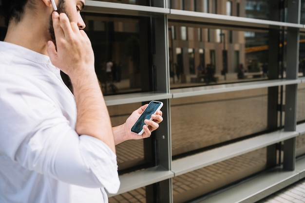 Homem de negócios que faz a videoconferência no smartphone e falando com o dispositivo viva-voz bluetooth