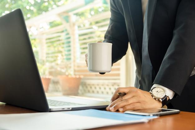 Homem de negócios que guarda a caneca de café com o portátil na tabela.