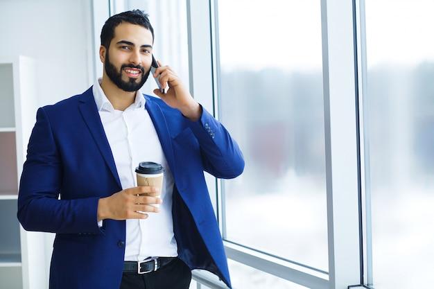 Homem de negócios que guarda o telefone celular e a xícara de café nos prédios de escritórios no fundo.