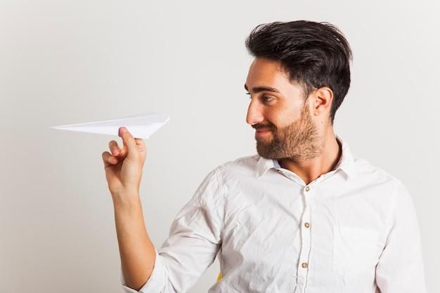 Homem de negócios que joga com avião de papel