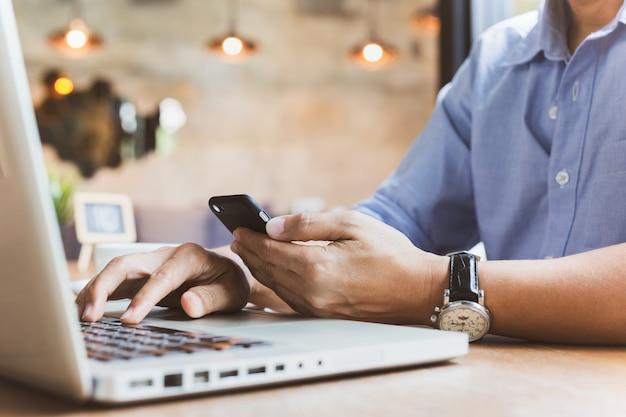 Homem de negócios que lê seu smartphone ao trabalhar no portátil.