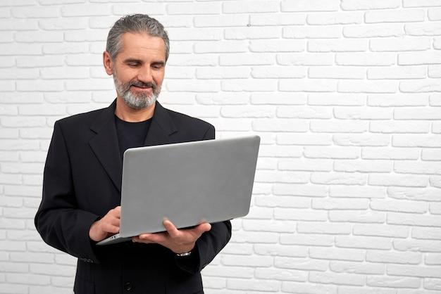 Homem de negócios que levanta com o caderno no estúdio.