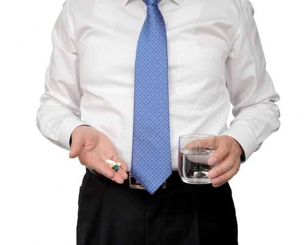 Homem de negócios que mantém o copo do comprimido e da água disponivel.