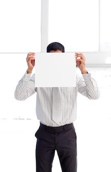Homem de negócios que mostra um cartão branco na frente do rosto